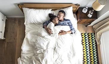 kuschelndes Paar im Bett ohne lästige Besucherritze